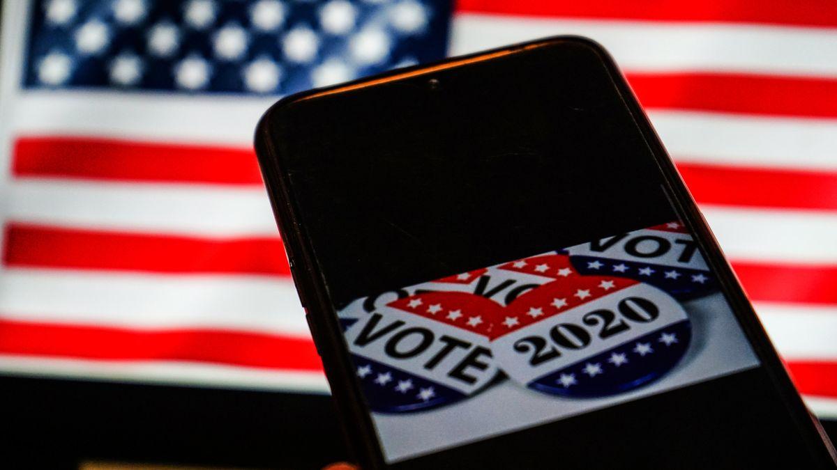 """Ein Handy mit """"Vote""""-Buttons auf dem Screen vor einer US-Flagge."""