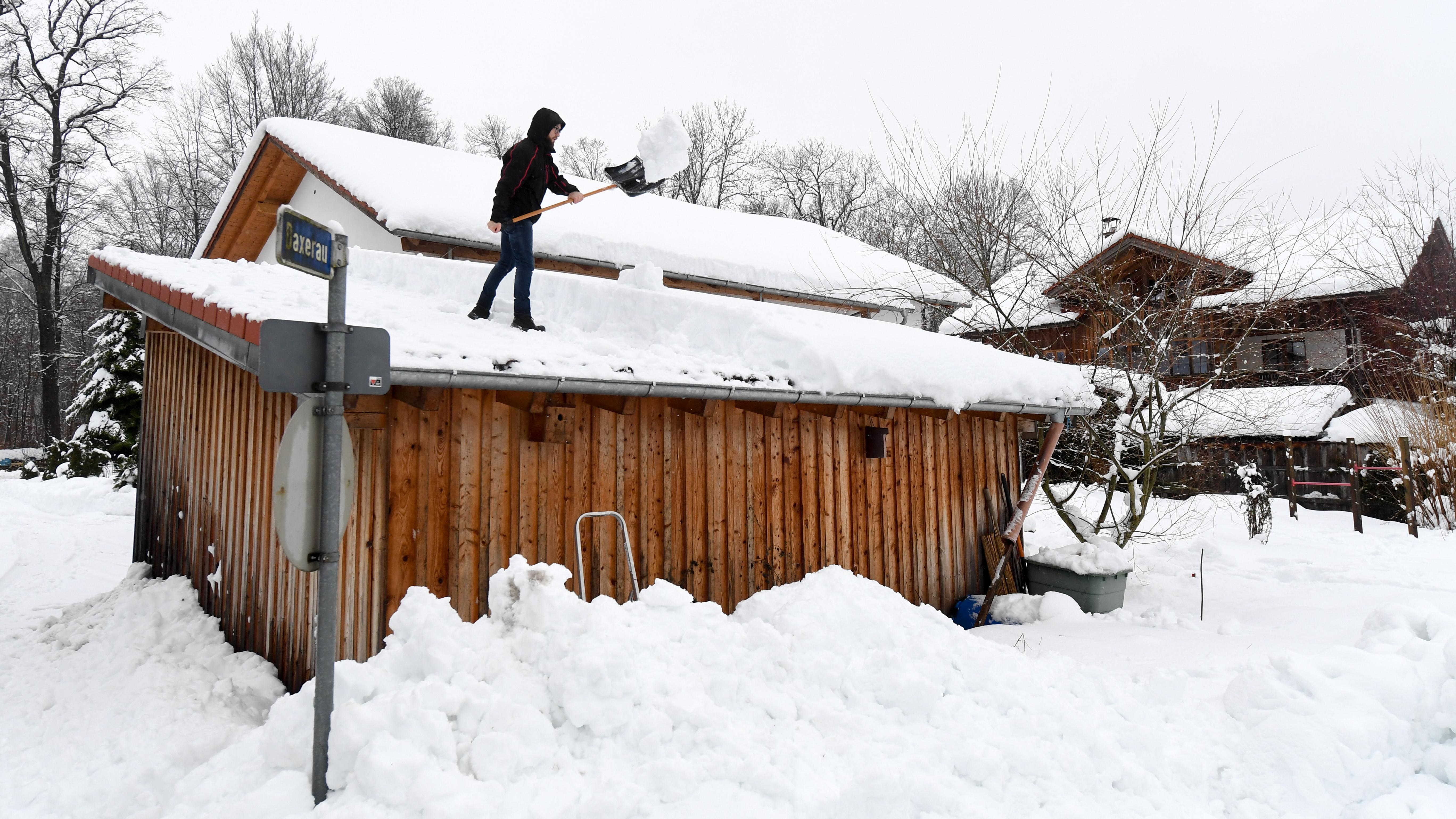 Mann befreit Dach von Schnee