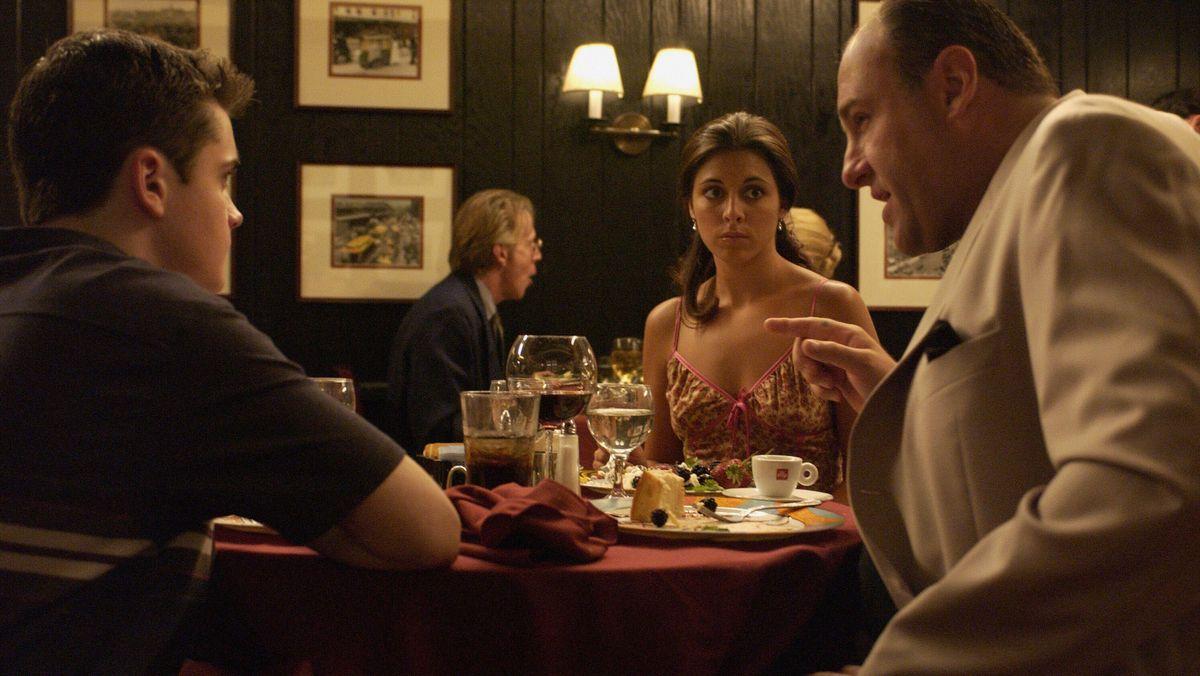 """Szene aus """"The Sopranos"""": Menschen sitzen an einem Tisch in einem Restaurant und unterhalten sich."""