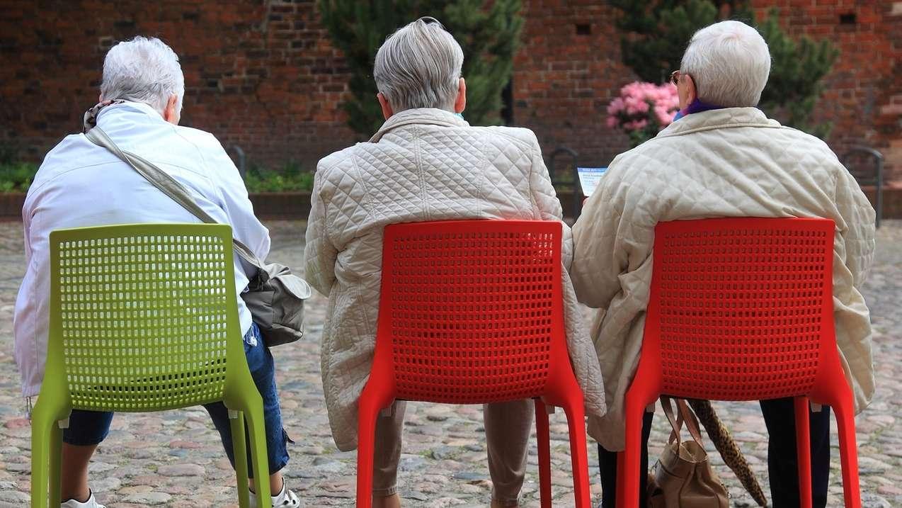 Drei Senioren sitzen auf roten und grünen Stühlen in einem Park.