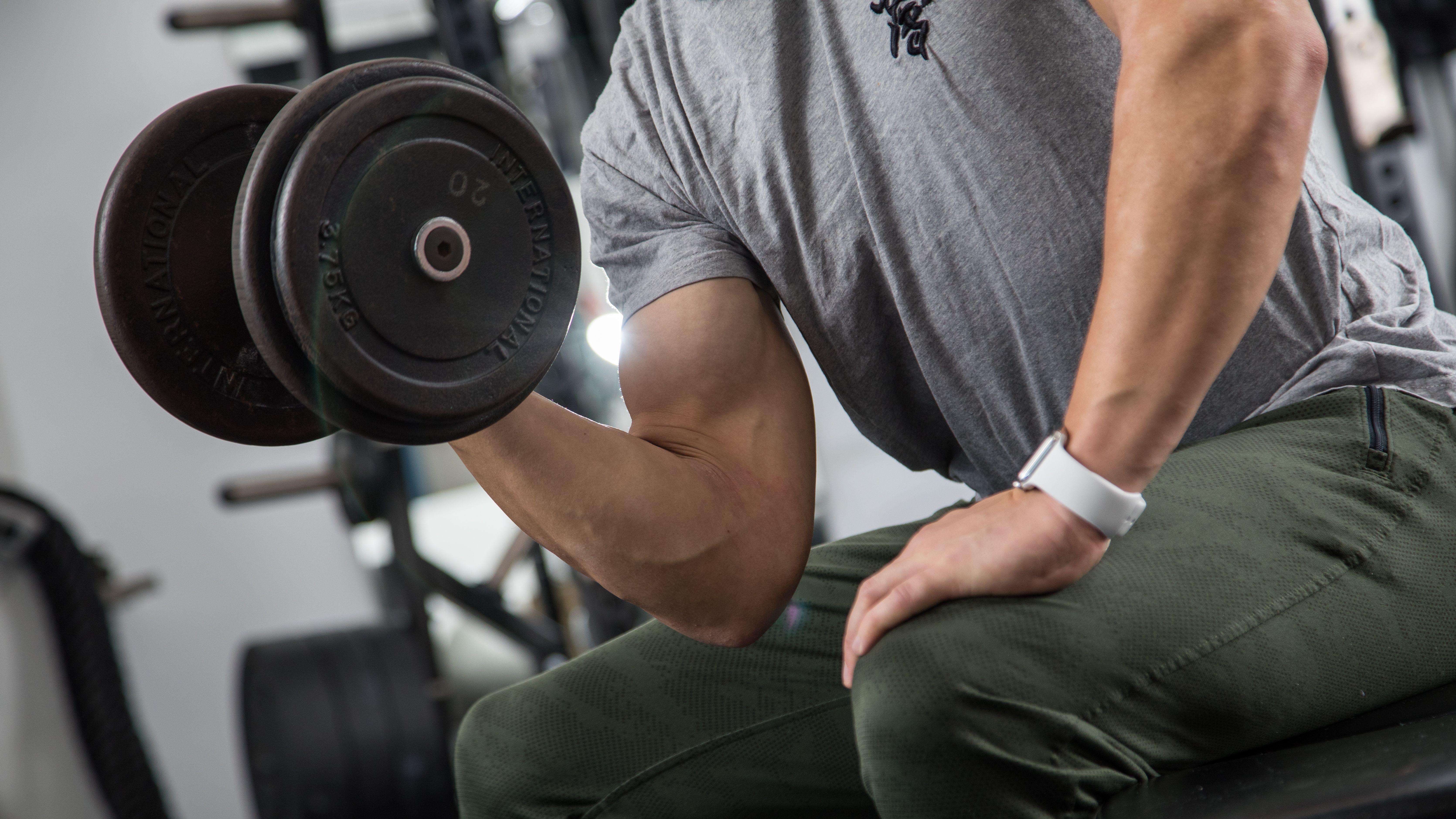 Ein Mann trainiert in einem Sportstudio mit einem Gewicht