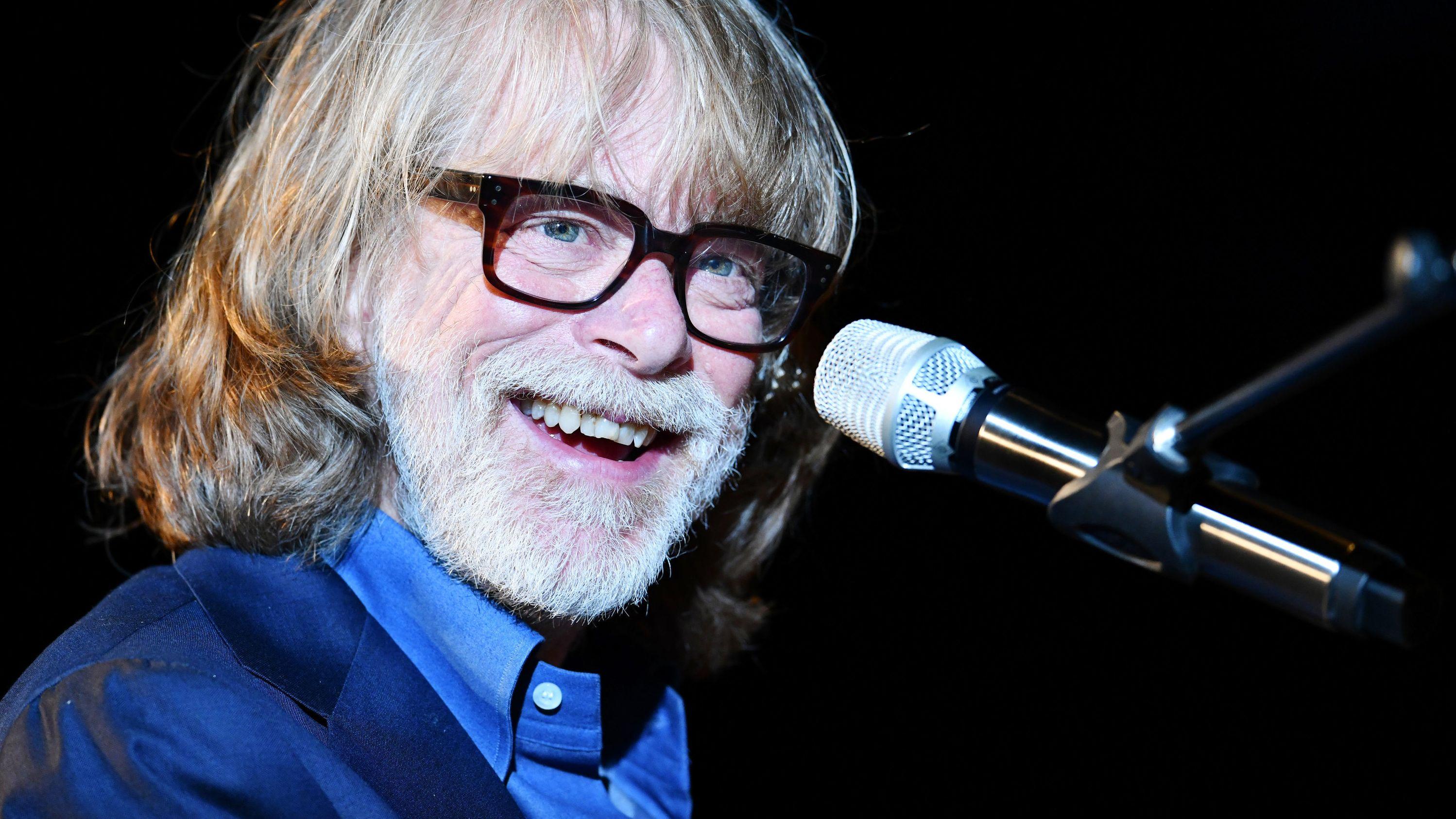 Helge Schneider lachend und mit Brille am Mikrofon bei einem Konzert in Heidelberg