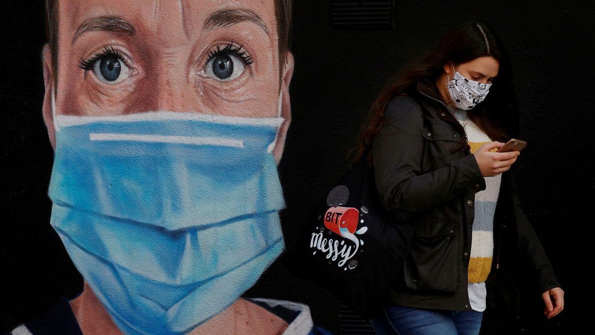 In Manchester geht eine Frau mit Mundschutz an einem Wandgemälde vorbei, das eine Krankenschwester zeigt, die ebenfalls einen Mundschutz trägt.