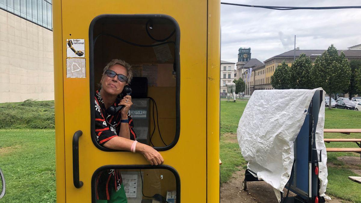 Doris Dörrie in einer Telefonzelle vor der Hochschule für Film und Fernsehen