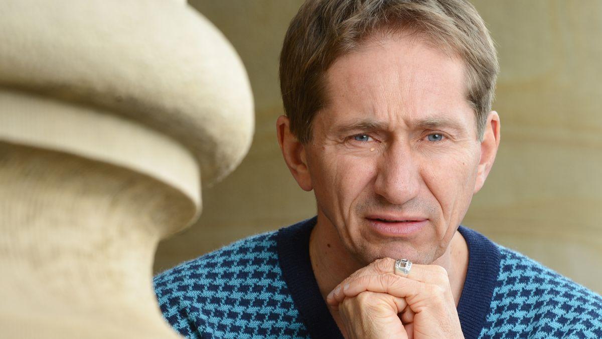 """Schorsch Kamerun, Regisseur und Sänger der Kultband """"Die Goldenen Zitronen"""", vor dem Opernhaus in Stuttgart neben einer Steinsäule"""