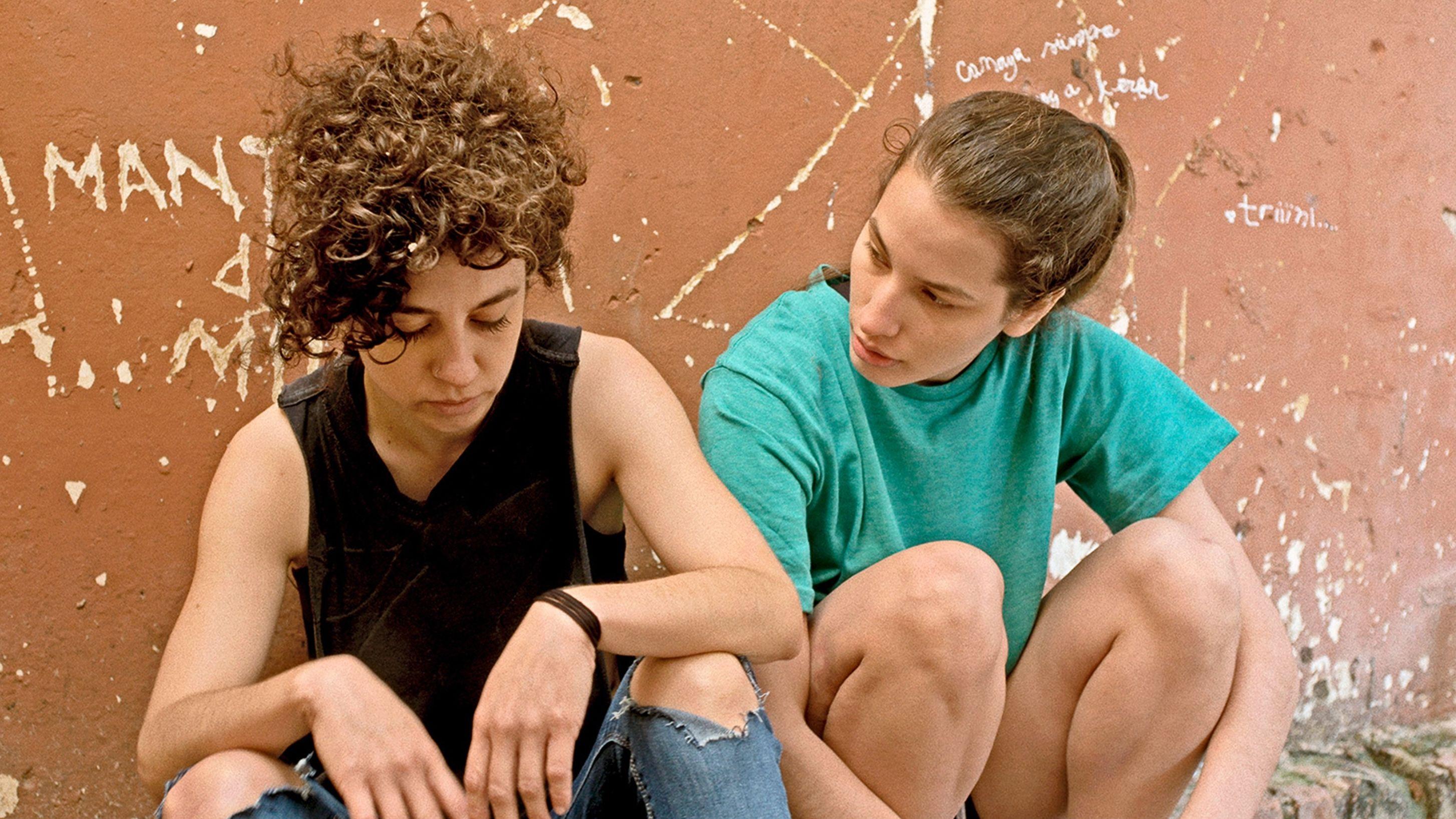 """Szenenfoto aus dem Film """"Las Mil y Una"""" mit Ana Carolina García und Sofia Cabrera: Zwei junge Frauen hocken vor einer ockerfarbenen Wand mit eingeritzten Schriften"""