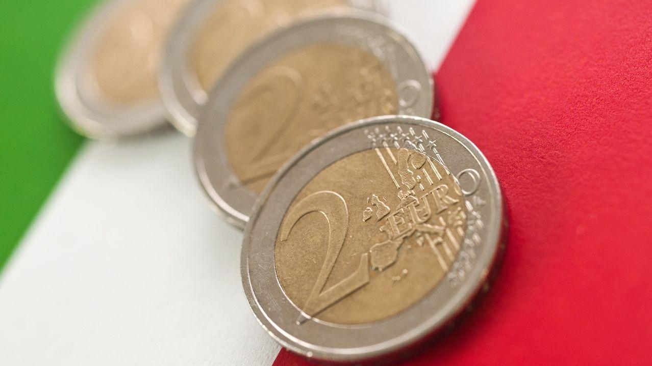 Euro-Münzen liegen auf einer italienischen Flagge.