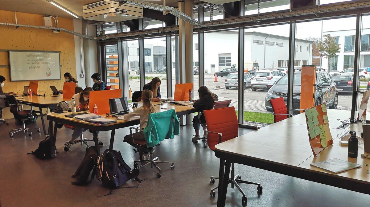 Ein moderner Workspace, in dem Schüler an Schreibtischen arbeiten.