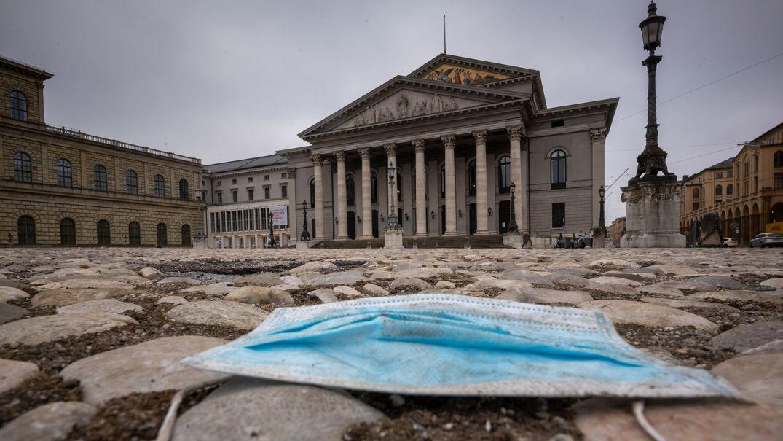 Auf dem Platz vor der Bayerischen Staatsoper in München liegt auf dem Kopfsteinpflaster ein medizinischer Mundschutz.