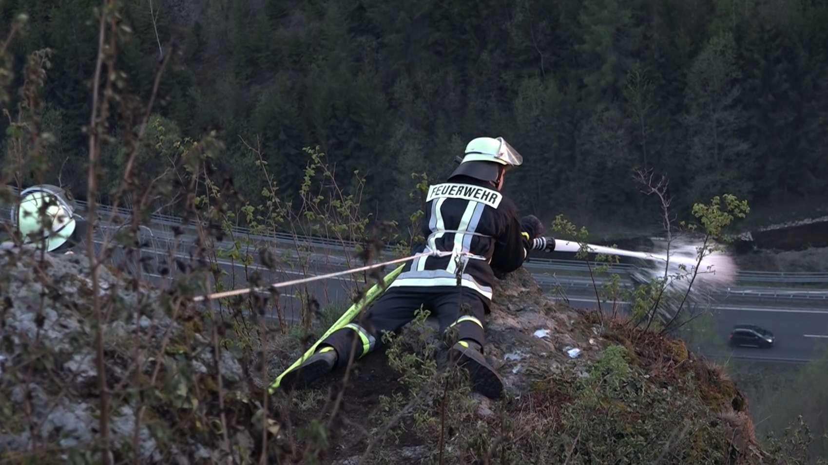 Feuerwehrleute löschen den Brand am Romansfelsen
