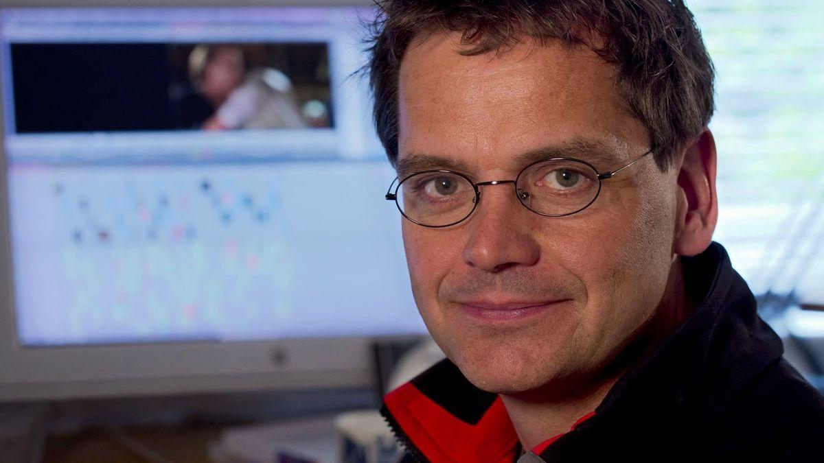 Ein Mann sitzt vor einem Bildschirm an dem ein Schnittprogramm für Film geöffnet ist.