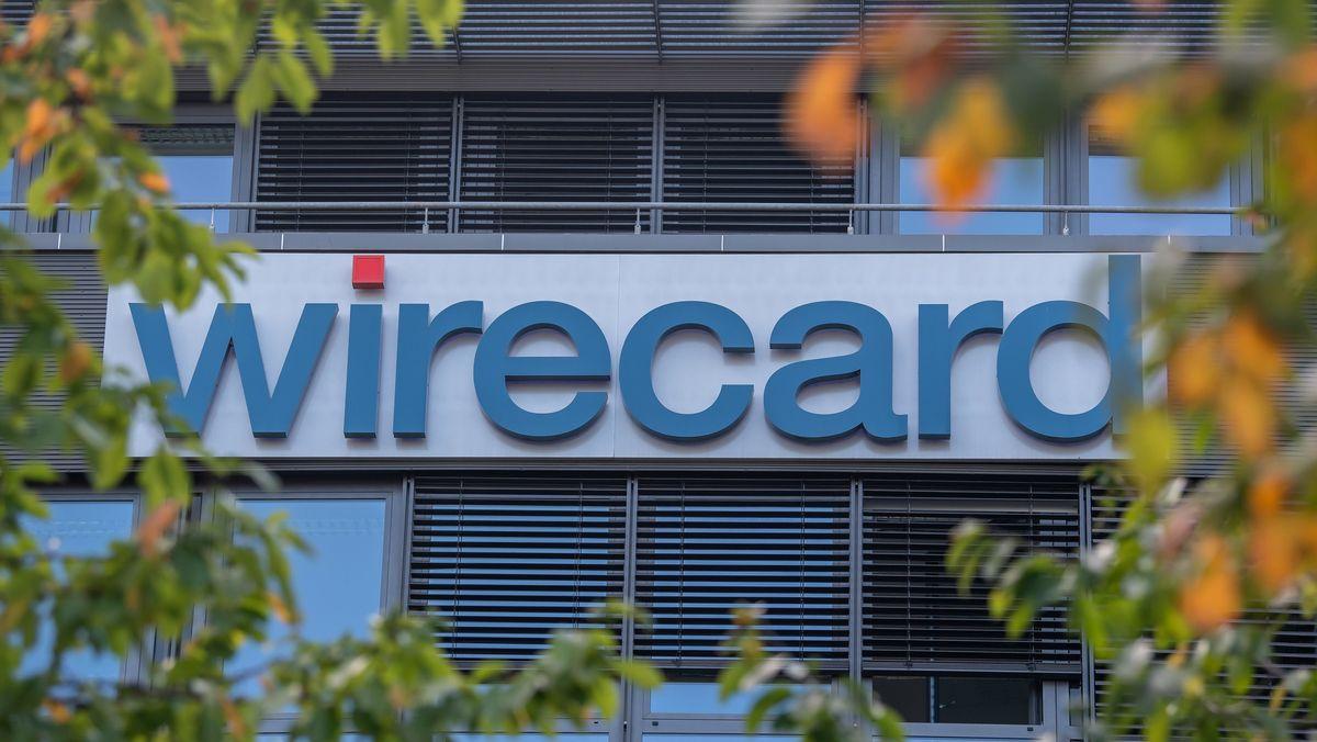 Der Firmenschriftzug Wirecard an der Firmenzentrale in Aschheim, im Vordergrund einige Äste