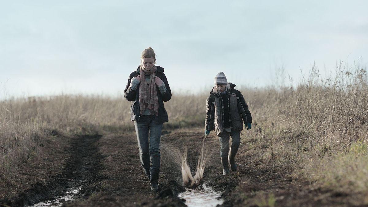 Die beiden Geschwister stapfen über einen matschigen Feldweg, der Bruder schlägt mit einem Stock in eine Wasserpfütze