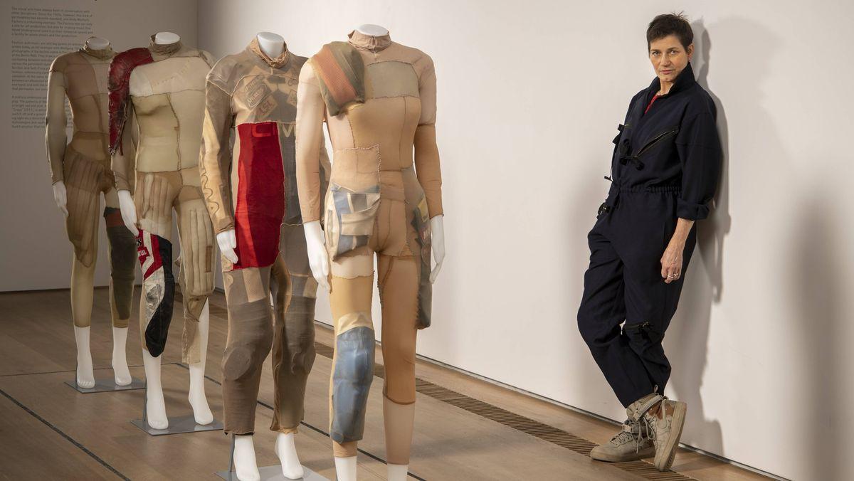 Alexandra Bircken vor ihrem Werk New Model Army, menschengroße Puppen in beigefarbenen Kostümen