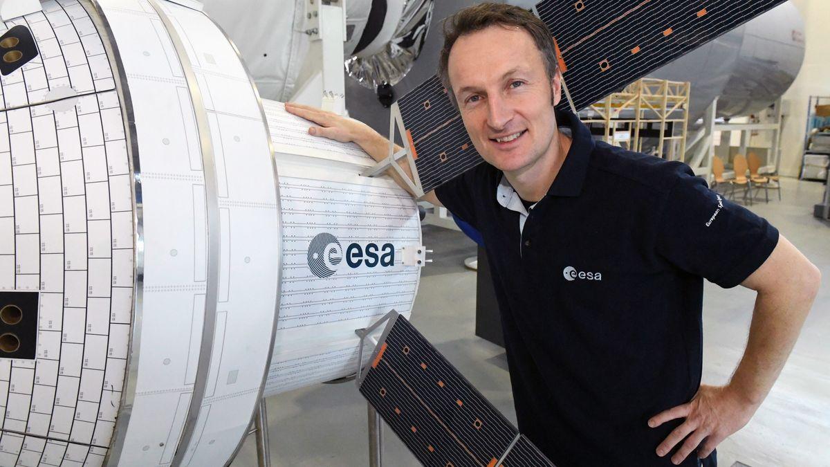 Der Astronaut Matthias Maurer steht im Europäischen Astronautenzentrum (EAC) auf dem Gelände der ESA neben einem Modell der Raumkapsel Orion.