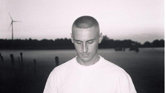 Schwarzweiß-Foto eines jungen Manns mit kurzen Haaren und gesenktem Blick