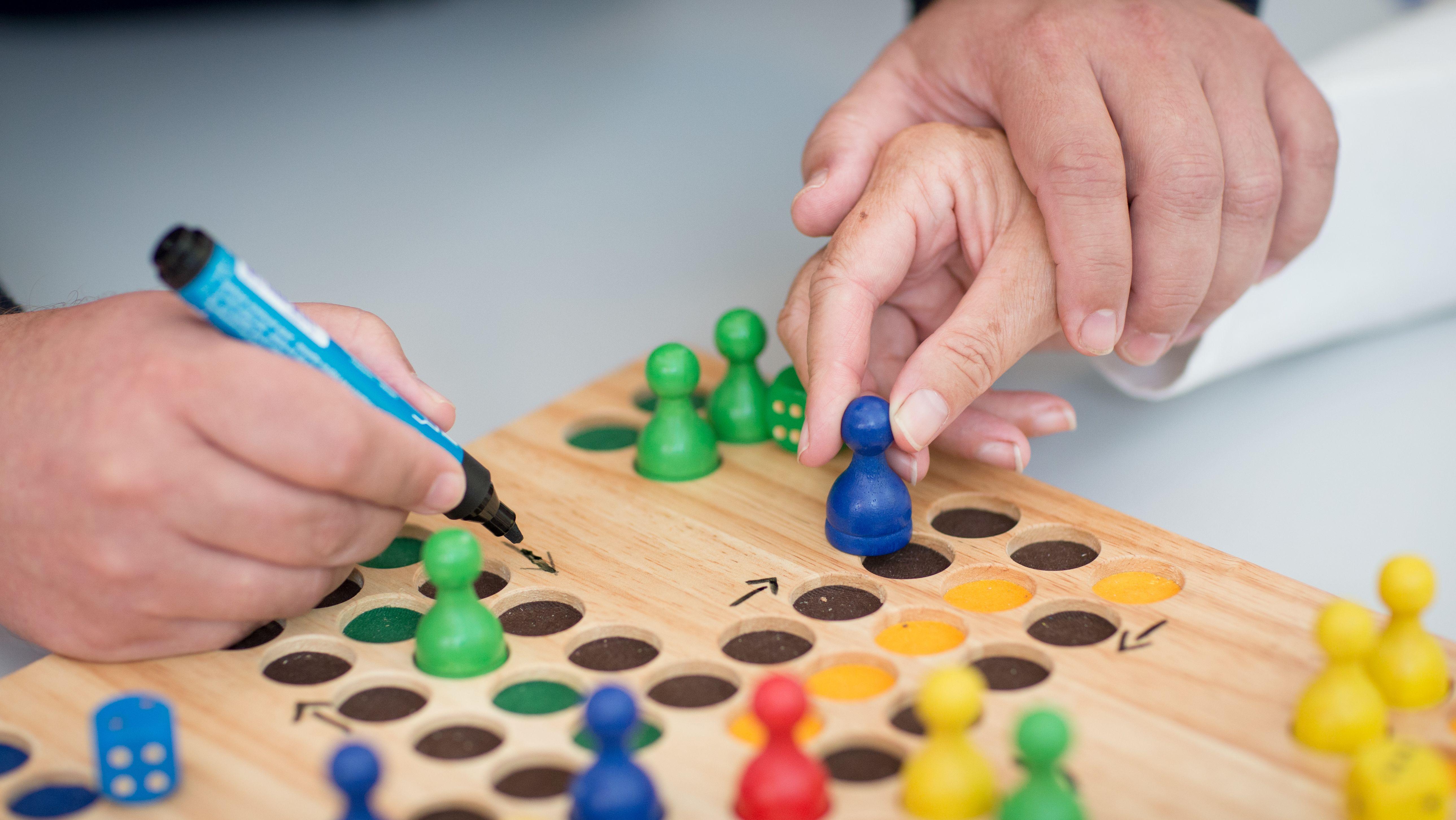 Spielbrett wird mit Pfeilen für an Demenz erkrankte Personen markiert