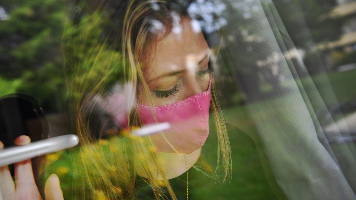 Eine junge Frau mit Mundschutz steht am Fenster in einem Zimmer und blickt wehmütig in die Ferne. (Symbolbild)