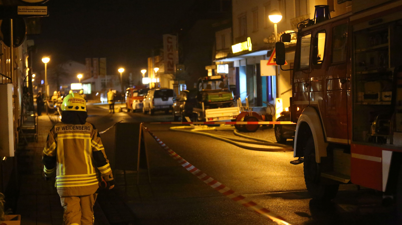 Einsatzkräfte stehen nachts in Weidenberg vor einer Bankfiliale auf der Straße