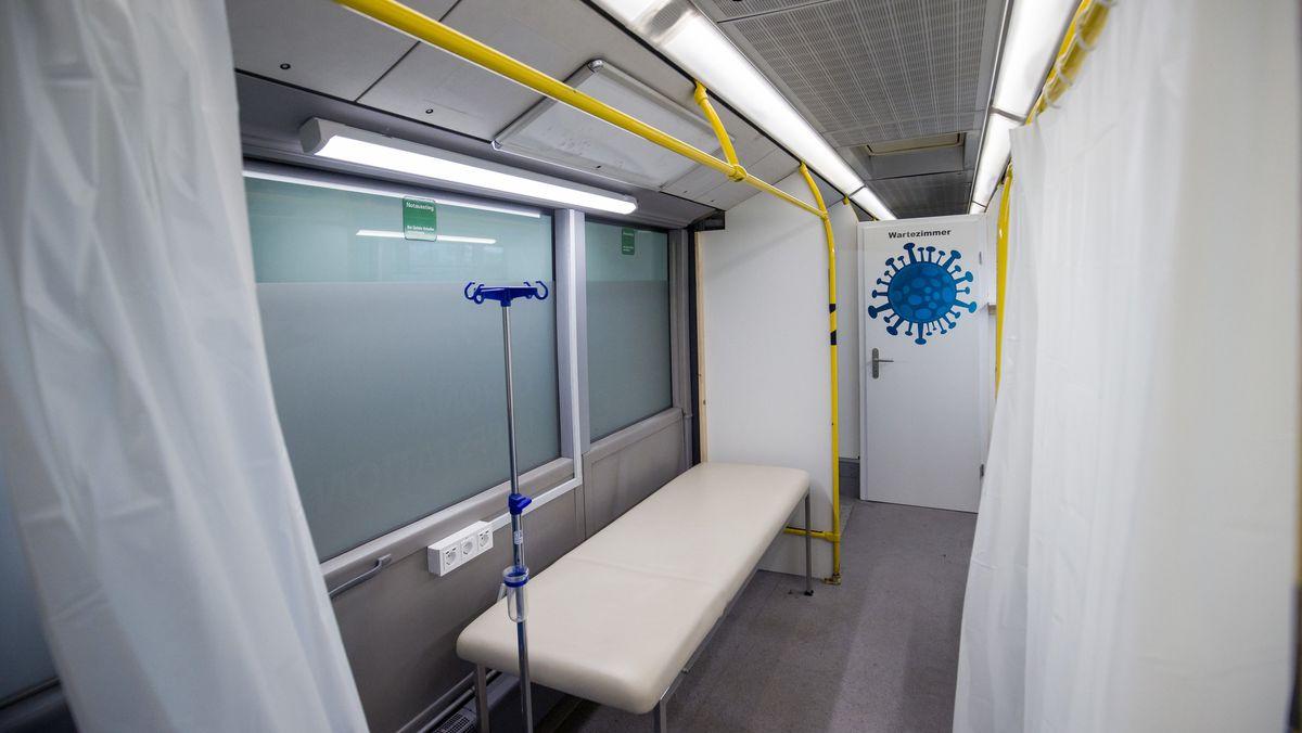 """Ein Bus, der zur """"mobilen Impfstation"""" umgebaut wurde, mit Liege und weißen Vorhängen"""