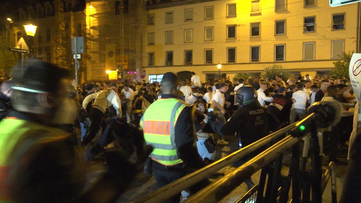 Polizei und randalierende Menschen auf der Straße in Augsburg