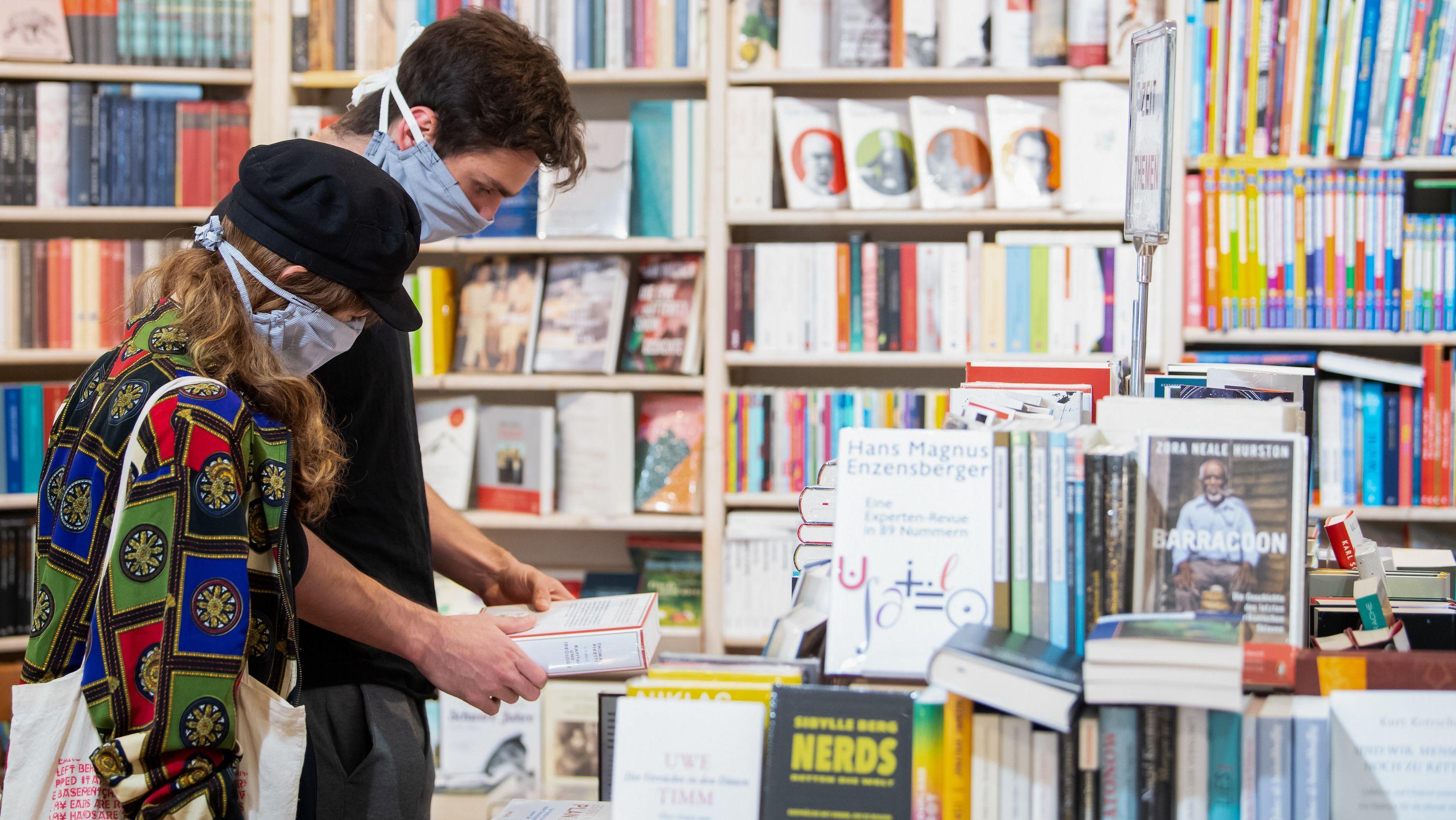 Eine Frau und ein Mann mit Mundschutzmasken stöbern in einer Buchhandlung