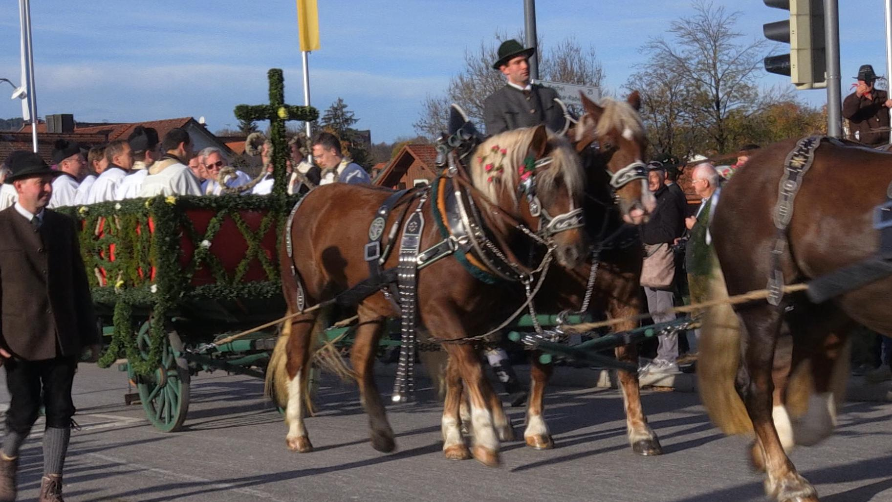 Ein Vierergespann zieht bei der Leonhardifahrt in Bad Tölz einen Wagen mit Ministranten.