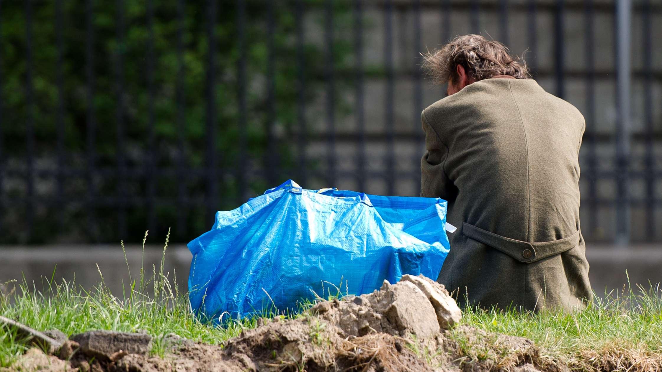 Obdachloser sitzt auf Wiese