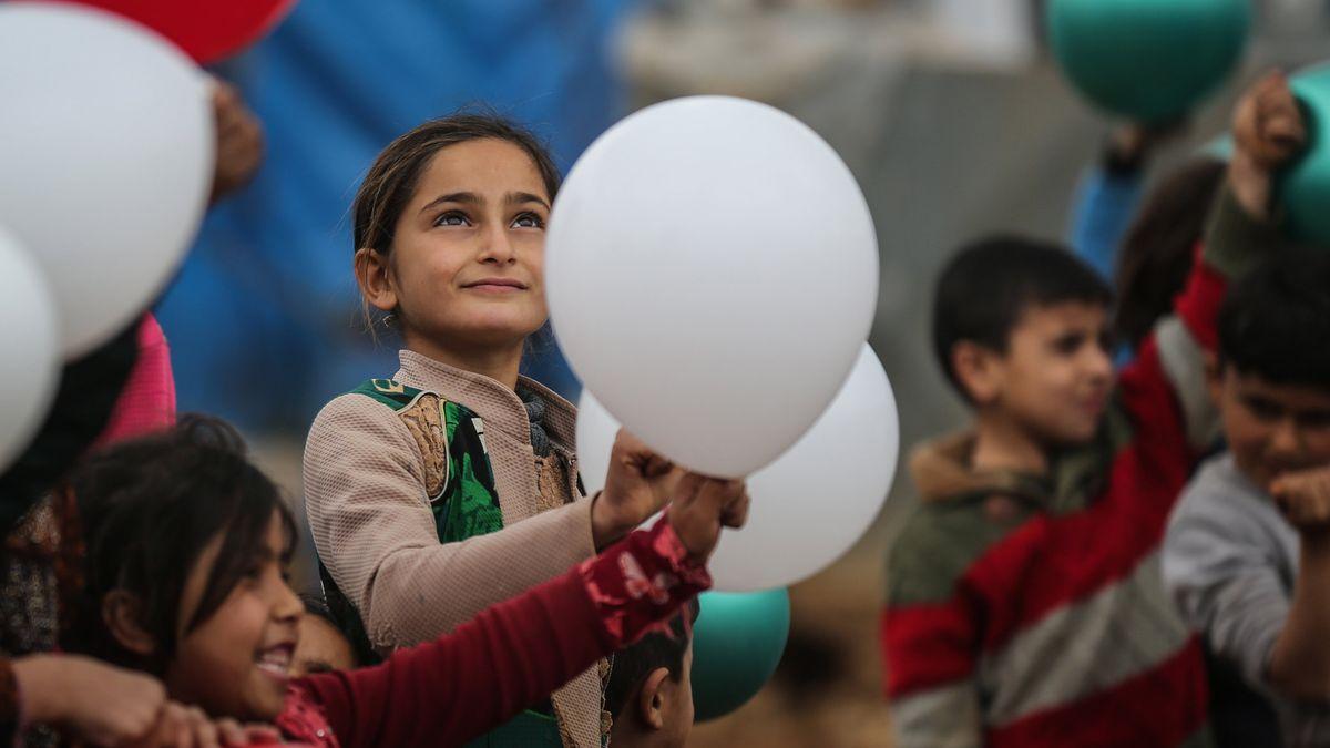 Syrische Kinder in einem Flüchtlingslager spielen mit Luftballons