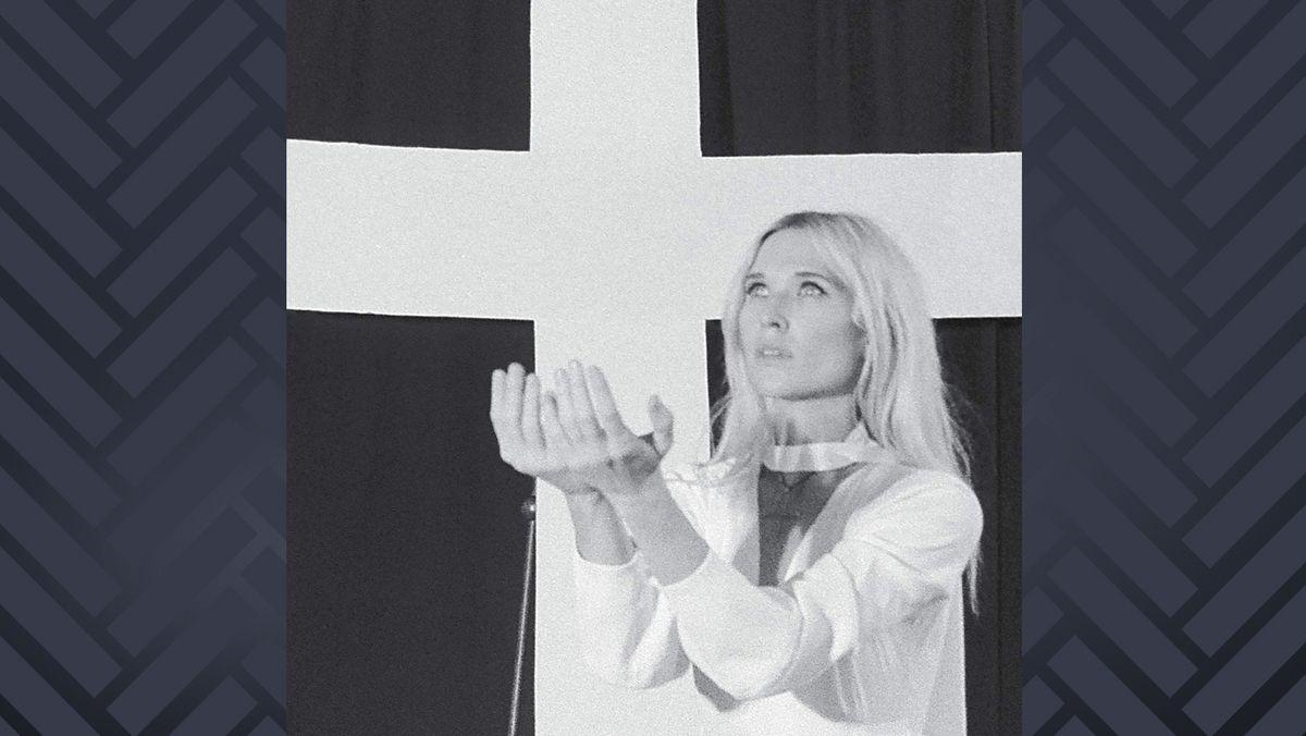 """Cover """"Mercy"""" von Natalie Bergman: Schwarzweiß-Aufnahme einer jungen Frau, die vor einer Fahne mit großem weißen Kreuz die Hände wie zum Gebet erhoben hat"""