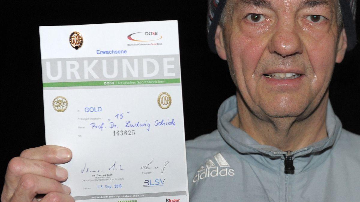 Ludwig Schick im Trainingsanzug zeigt eine Urkunde.