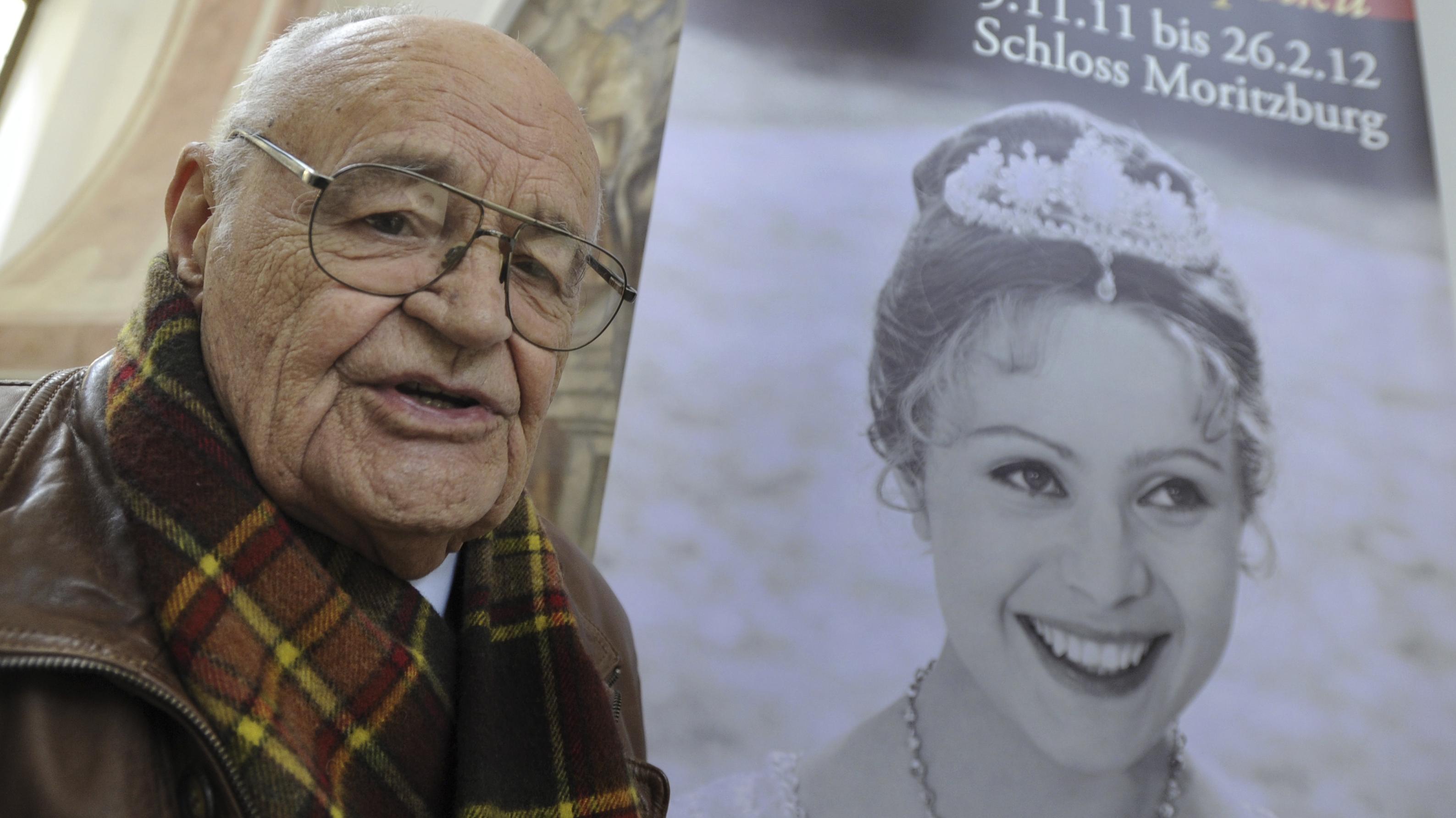 """Regisseur Vaclav Vorlicek im Jahr 2011 in Schloss Moritzburg. Neben ihm ist ein Plakat von """"Drei Haselnüsse für Aschenbrödel""""."""