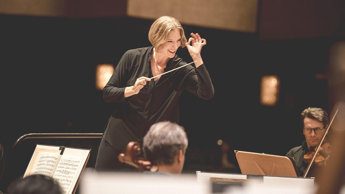 Joana Mallwitz mit Dirigentenstab vor Musikern.