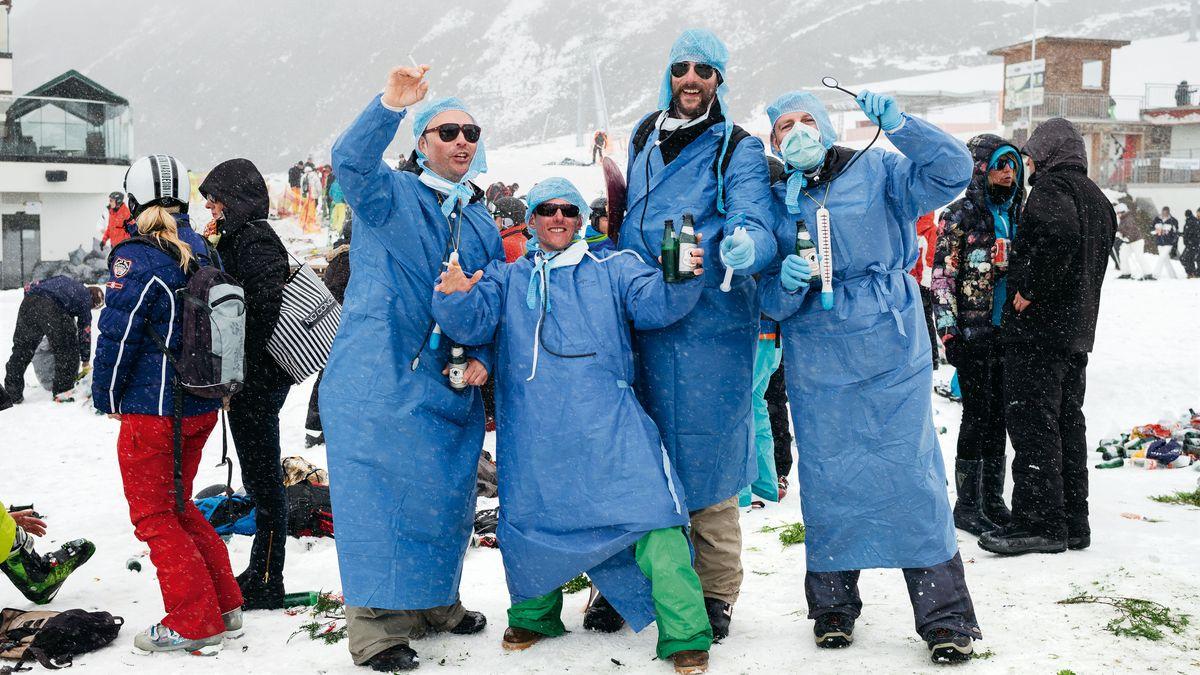 Eine Männergruppe posiert bei einer Après-Ski-Party in der Verkleidung eines Klinikarztes mit Sonnenbrille und Bierflaschen in der Hand.