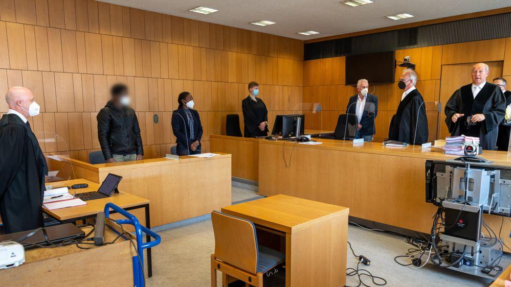 Blick in den Gerichtssaal im Landgericht Traunstein, links der Angeklagte mit Anwalt und Dolmetscherin, ganz rechts im Bild der vorsitzende Richter, alle mit FFP2-Masken.