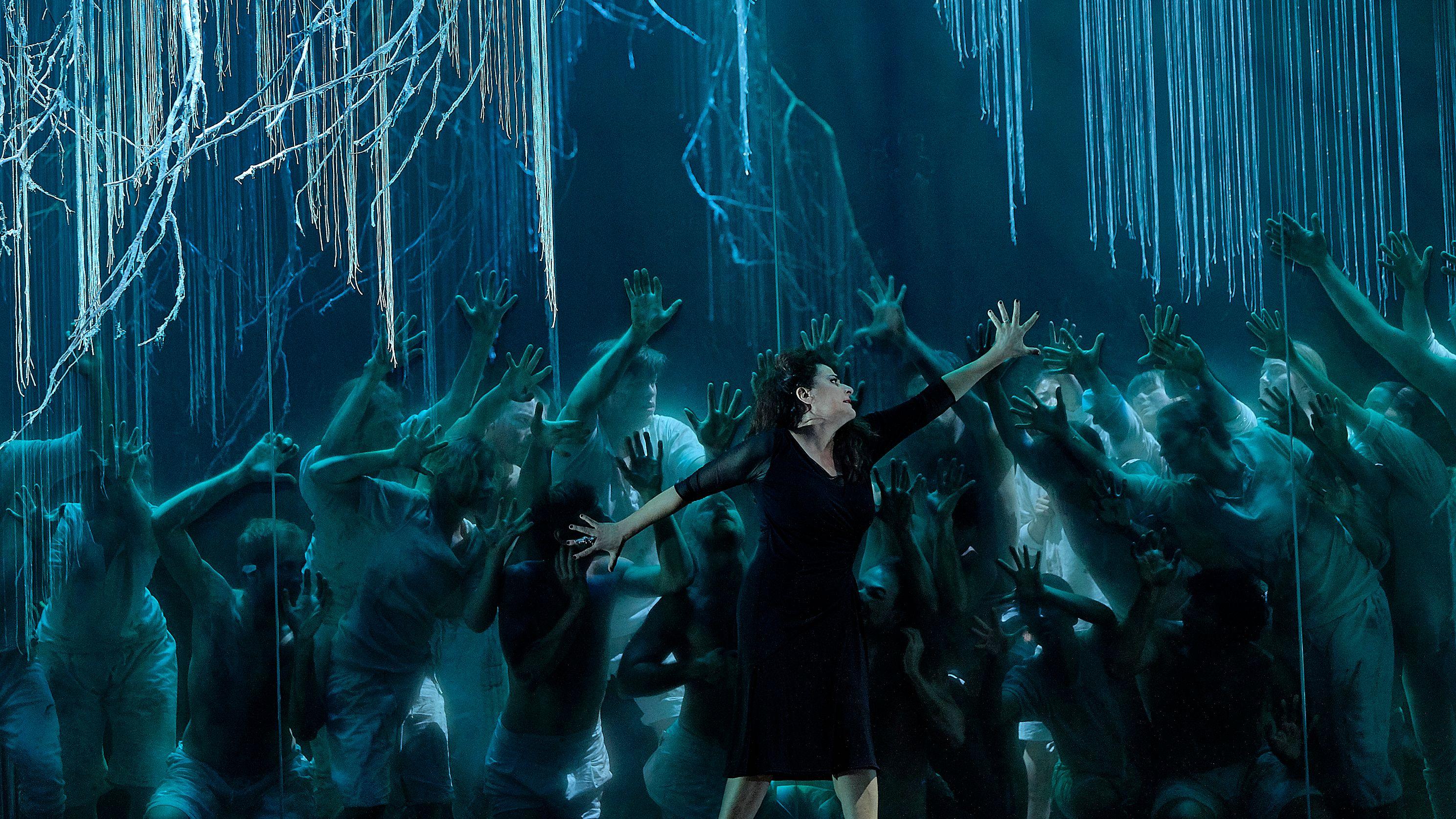 """Bild einer Szene von """"Alcina"""" bei den Salzburger Pfingstfestspielen: Cecilia Bartoli (Alcina) mit weit ausgestreckten Armen vor einem blauen Bühnenbild, Tänzern und dem Chor"""