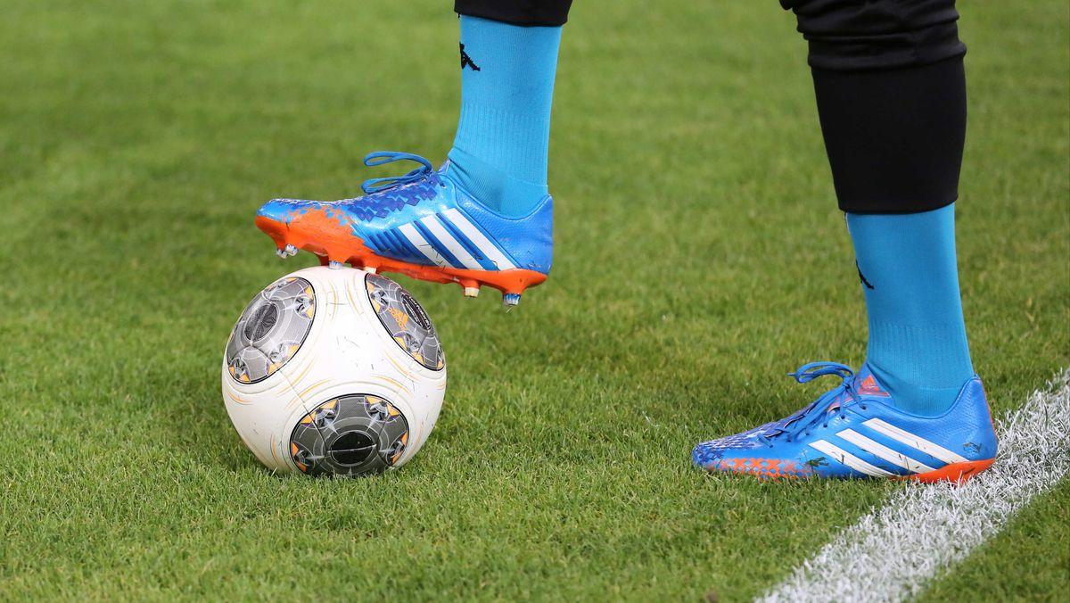Beine eines Fußballers und ein Fußball