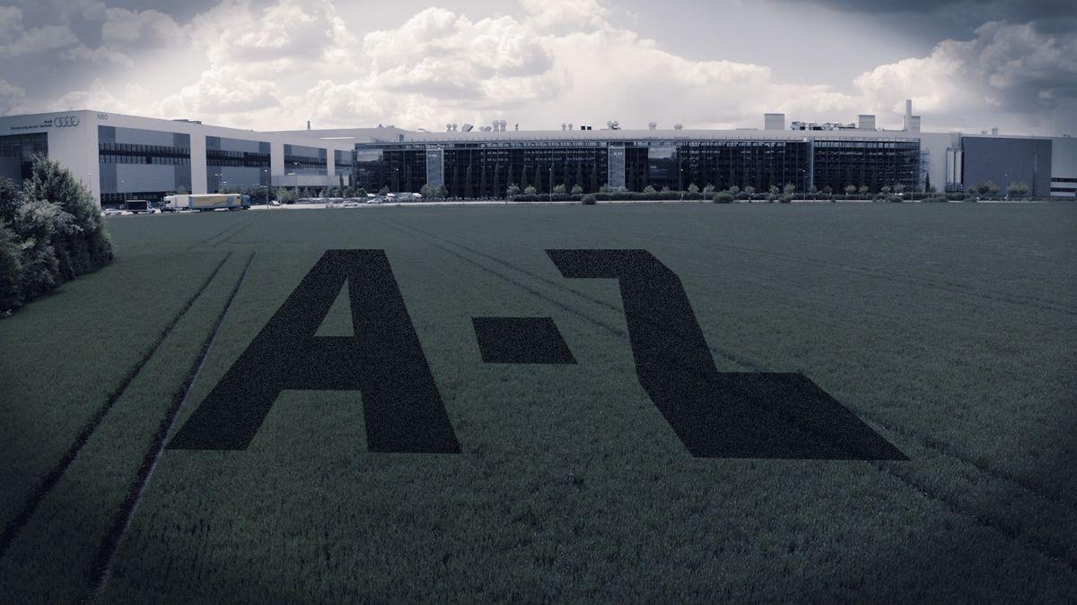 """Ein landwirtschaftliches Feld, auf dem """"A-Z"""" projiziert ist, im Hintergrund: Audi-Gebäude in Ingolstadt."""