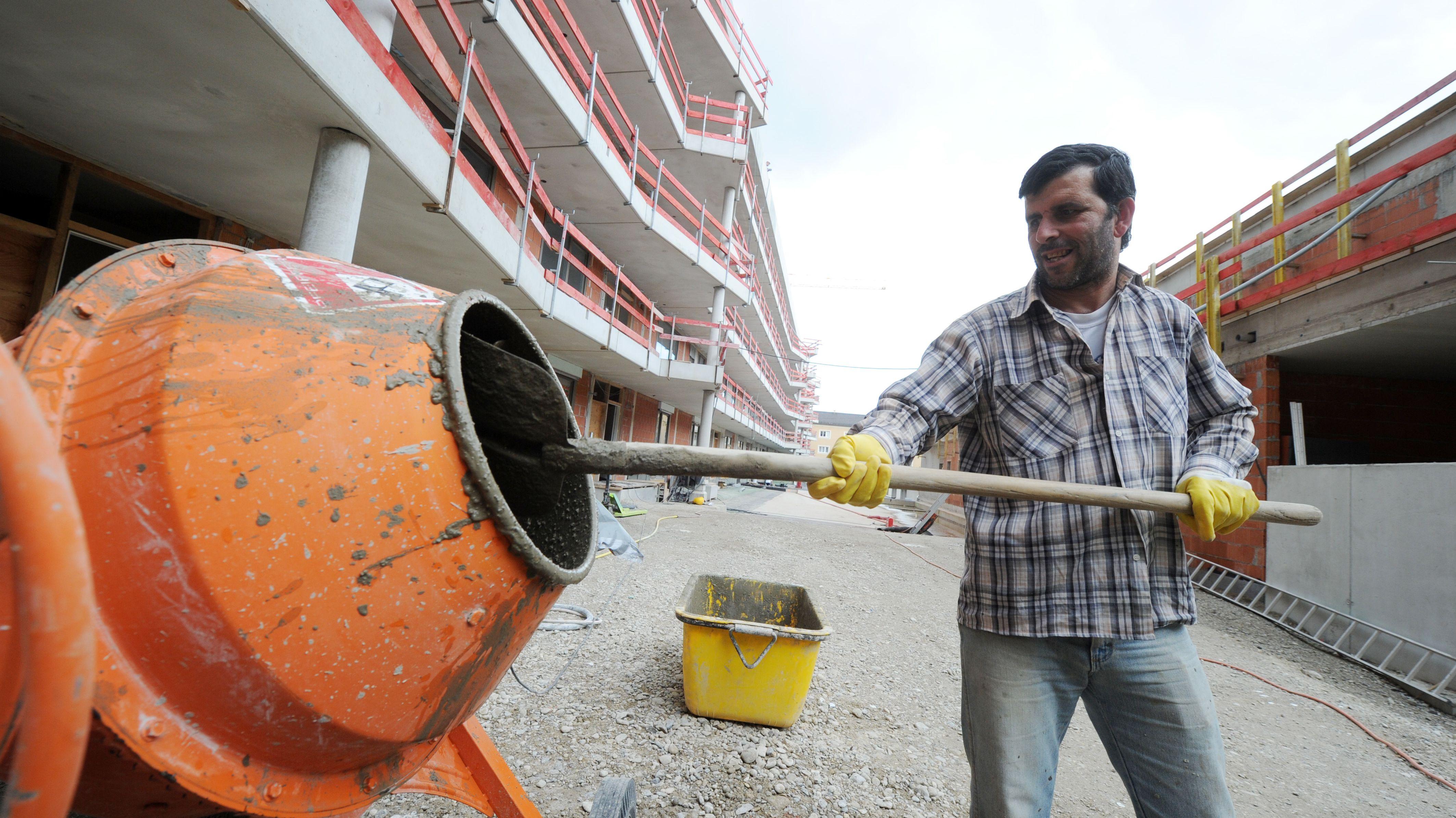 Ein Bauarbeiter befüllt mit einer Schaufel eine Betonmischmaschine.