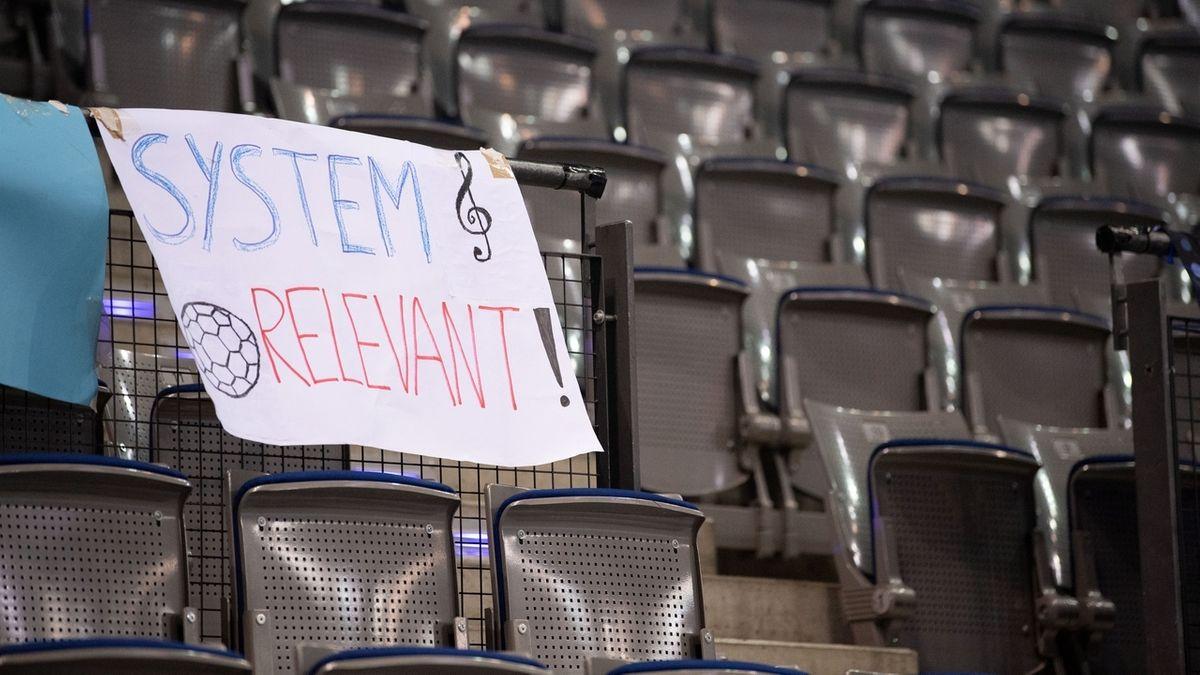 """Ein Plakat mit den Worten """"System relevant"""" hängt bei einem Handballspiel am leeren Zuschauerrang."""