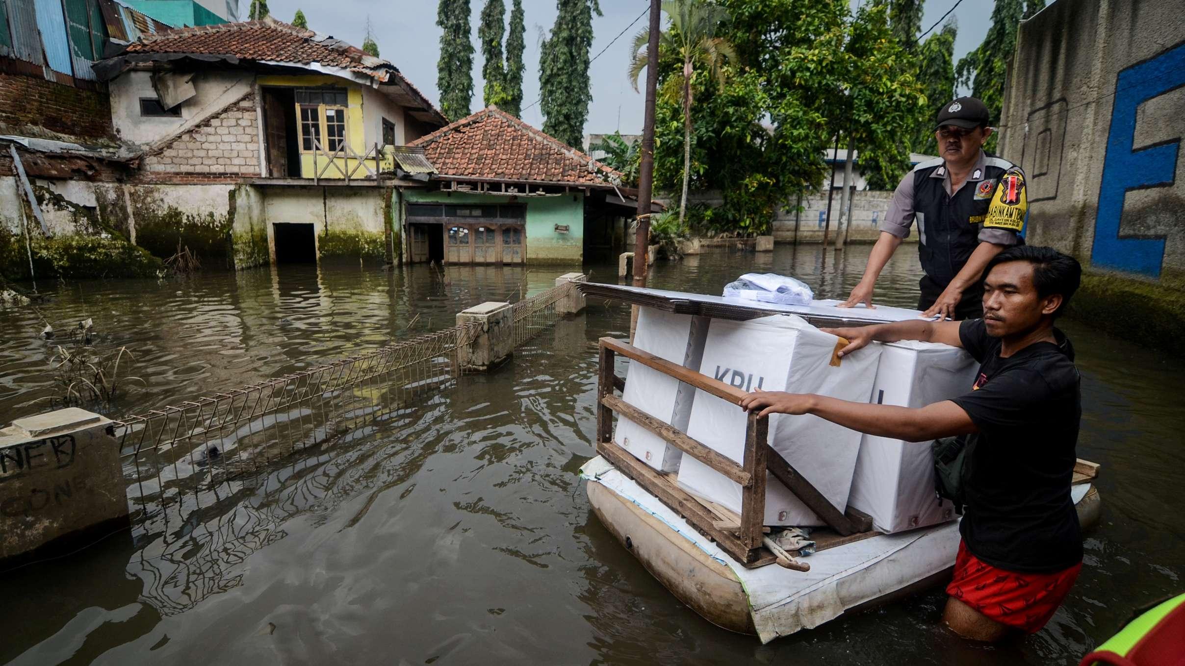 Ein Wahlhelfer und ein Beamter versuchen Wahlurnen zu transportieren