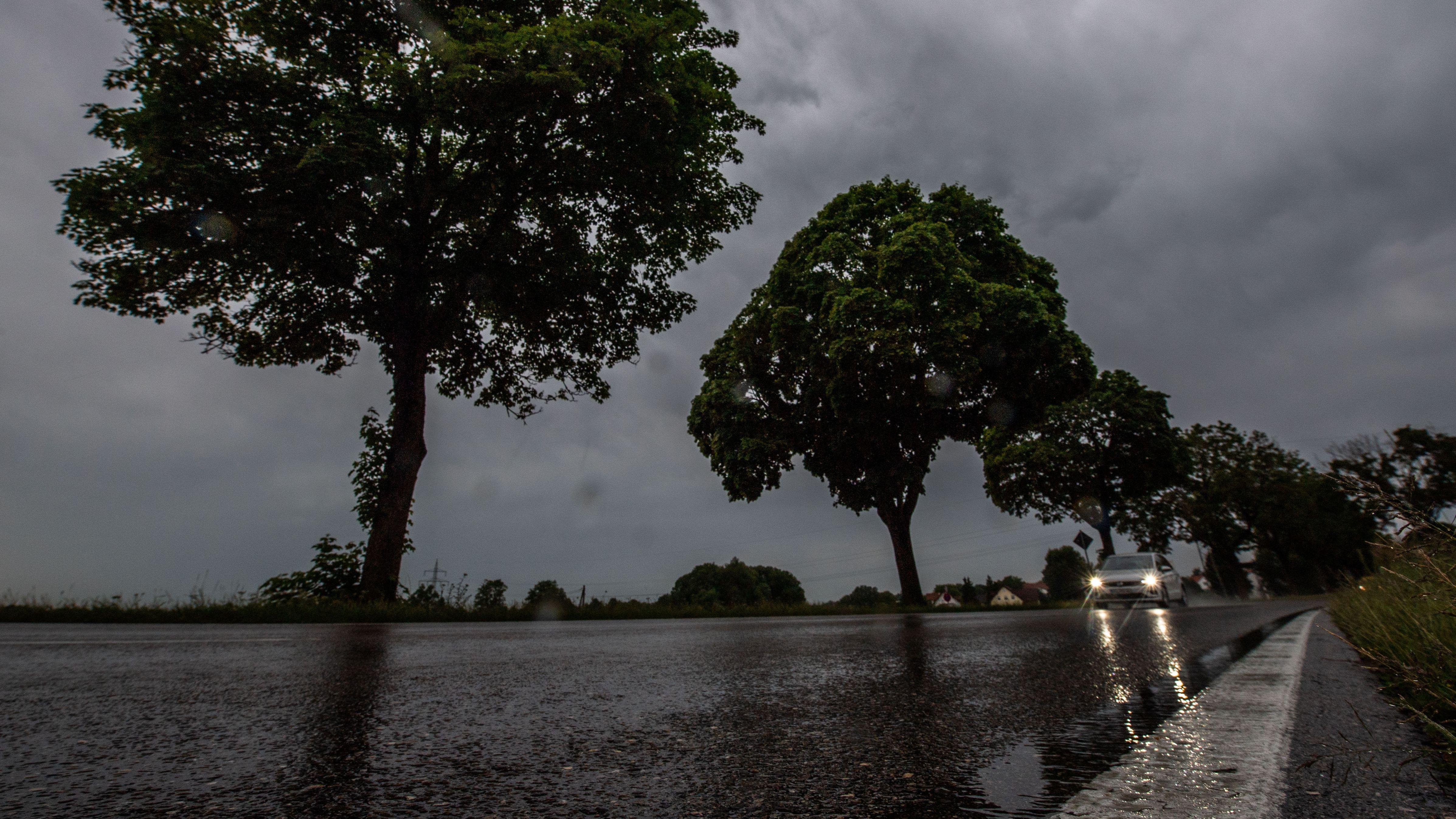 Ein Auto fährt auf einer regennassen Landstraße bei Allershausen
