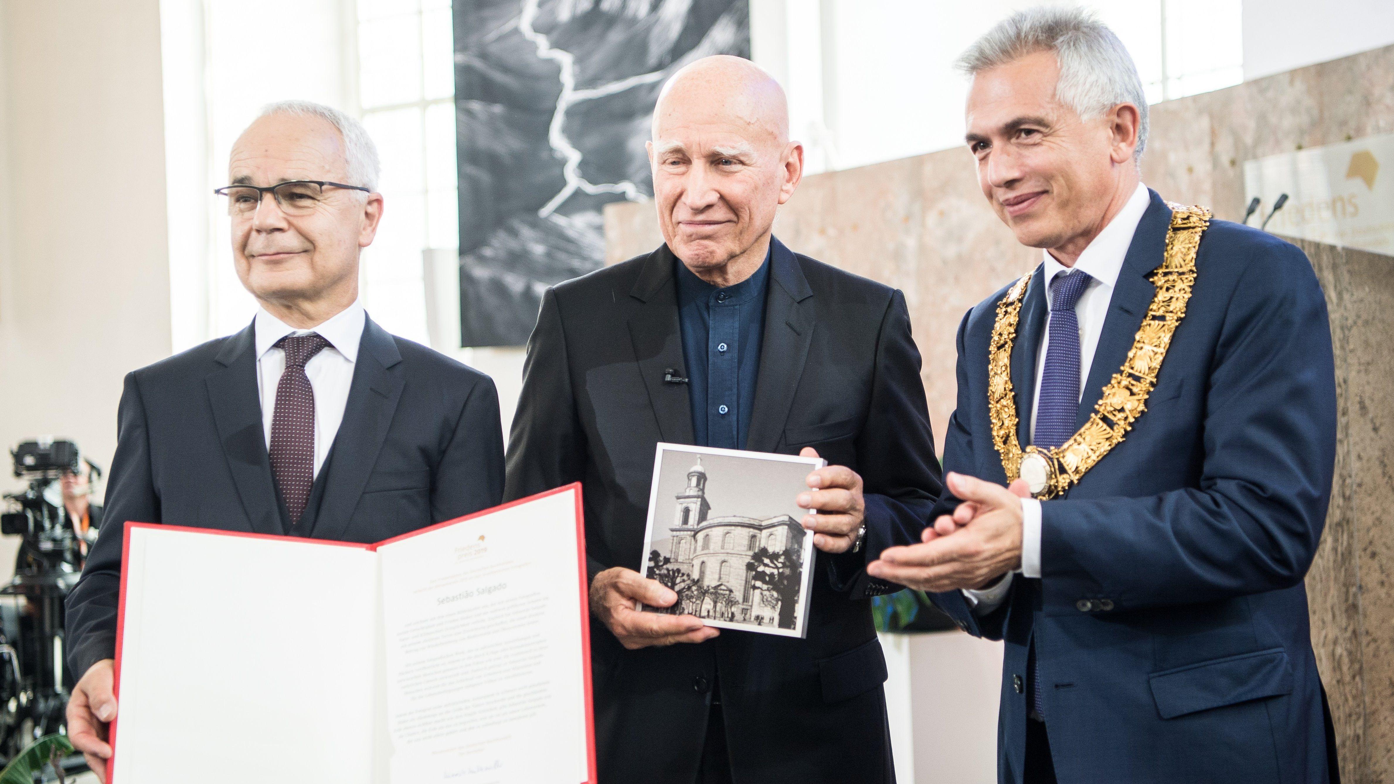Heinrich Riethmüller (l-r), Vorsteher des Börsenvereins des Deutschen Buchhandels, Sebastiao Salgado, Fotograf, und Peter Feldmann (SPD), Oberbürgermeister von Frankfurt am Main, stehen nach der Preisverleihung in der Paulskirche zusammen.