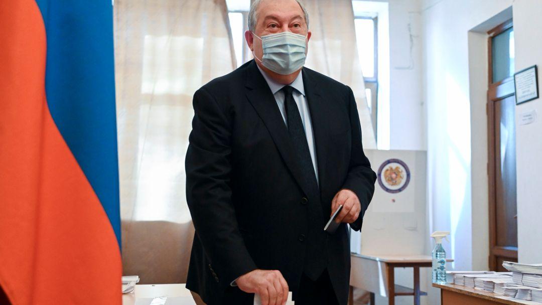 20.06.2021, Armenien, Yerevan: Armen Sarkissjan, Präsident von Armenien, wirft seinen Stimmzettel in eine Wahlurne in einem Wahllokal während einer Parlamentswahl. Sieben Monate nach dem Krieg um die Konfliktregion Bergkarabach wählt die krisengeschüttelte Südkaukasusrepublik Armenien ein neues Parlament. Foto: Davit Hakobyan/PAN Photo/AP/dpa +++ dpa-Bildfunk +++