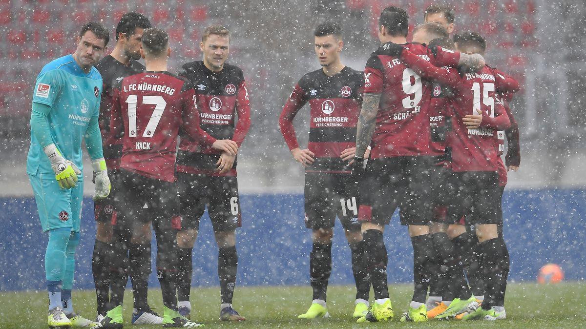 Spieler des 1. FC Nürnberg stehen im Schneegestöber zusammen auf dem Platz