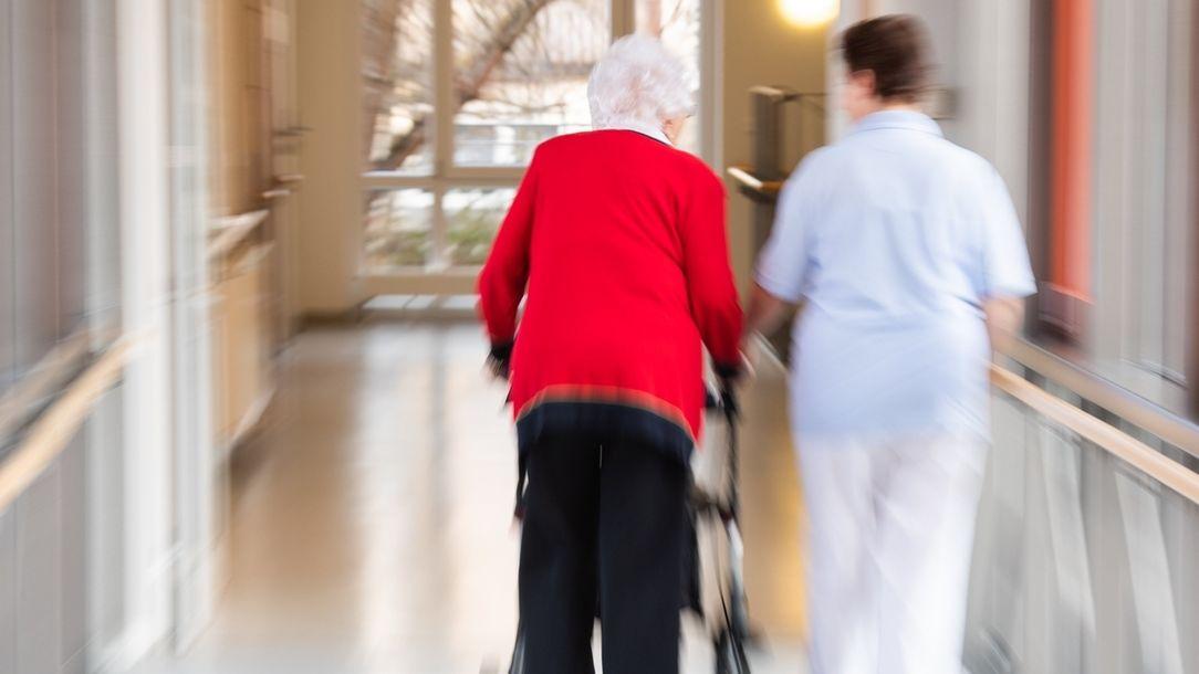Eine Pflegerin geht mit einer Bewohnerin des Pflegeheims und einem Rollator über den Flur