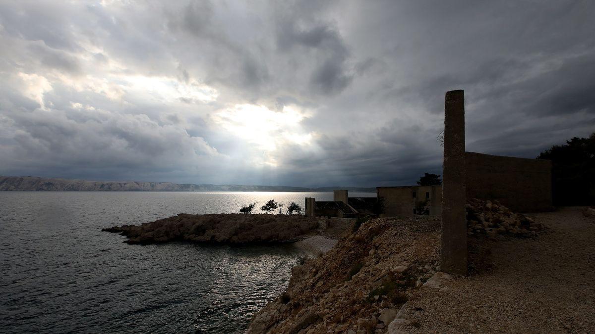 Ruinen und Felsen an der Küste einer verlassenen Insel und ein Himmel mit dicken Wolken, durch die sich an einer Stelle das Sonnenlich kämpft.