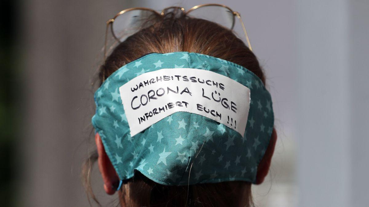 """Eine Demonstrantin trägt eine Maske mit dem Schriftzug """"Wahrheitssuche - Corona Lüge - Informiert euch!!!"""" auf dem Hinterkopf"""