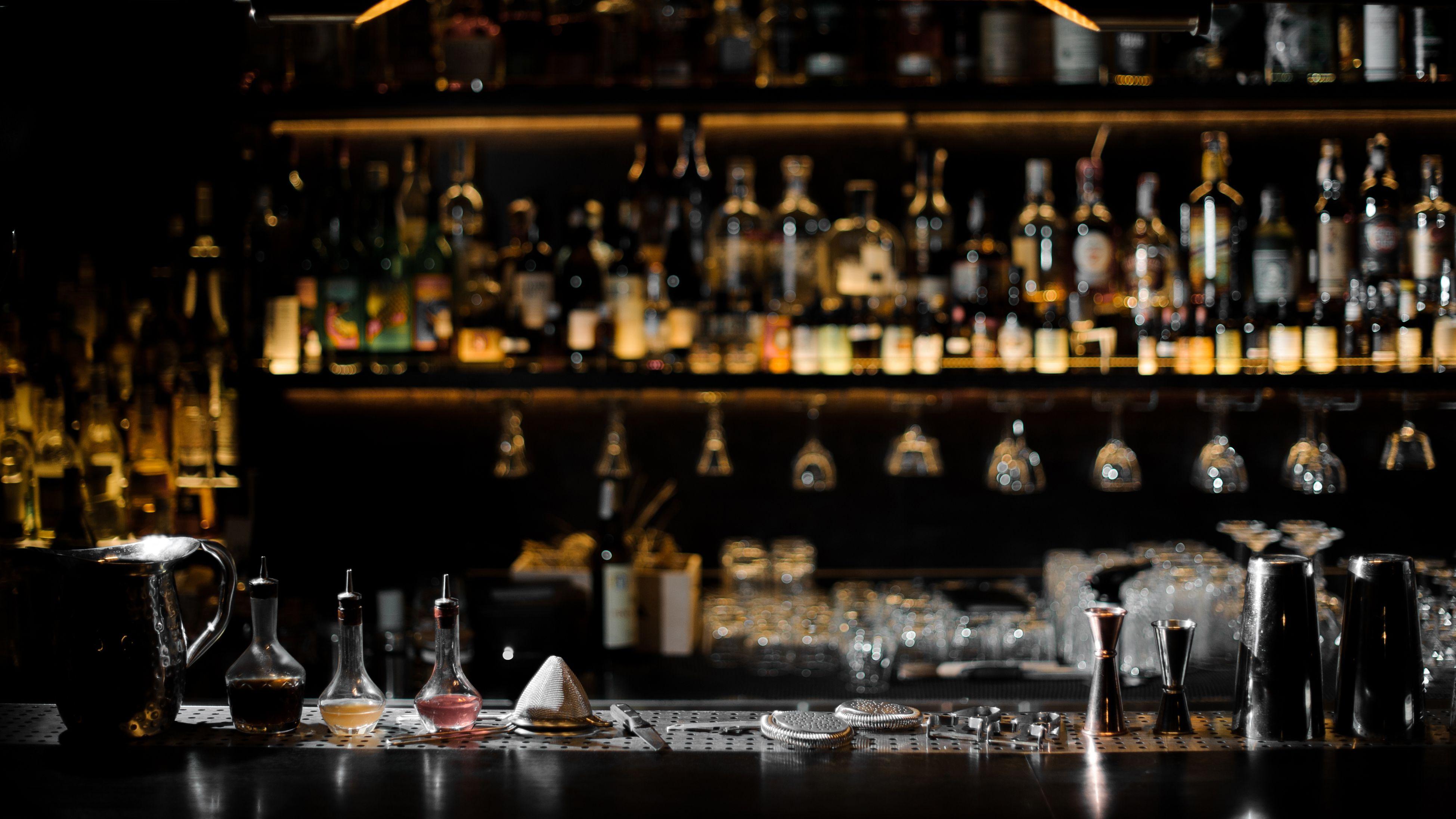 Eine dunkle Bar mit vielen Flaschen und allerlei Säften und Alkoholsorten zum Mixen