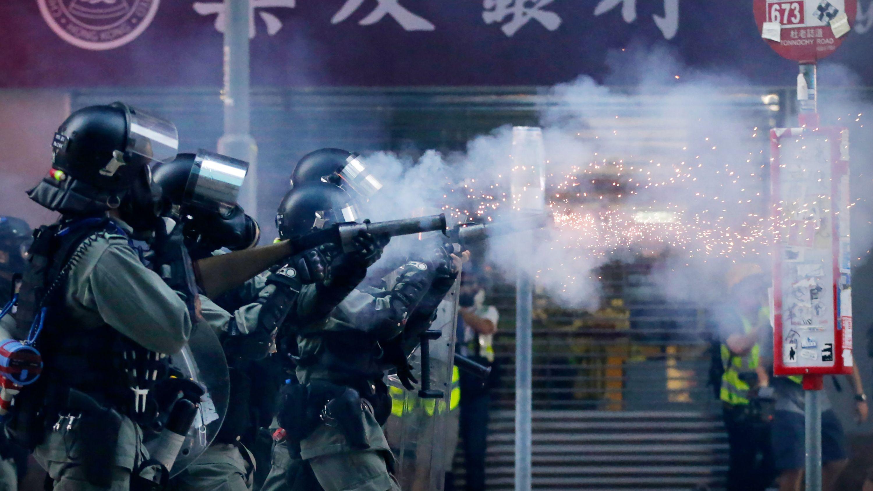 Polizisten mit Gasmasken schießen bei einer Demonstration in Hongkong mit Tränengas auf Demonstranten.